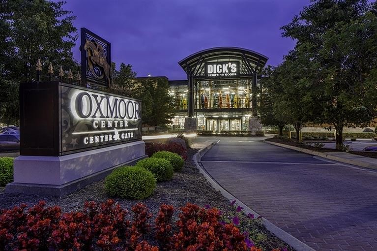 An exterior entrance at Oxmoor Center is lit up at night, surrounded by flowers, plants, and trees
